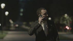 Parler amical d'homme d'affaires par le téléphone en parc de ville banque de vidéos