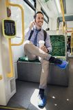 Parler au téléphone tout en permutant en le tram Images stock
