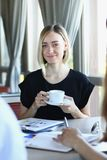 Parler blond de femme aux amis dans un café Photographie stock libre de droits