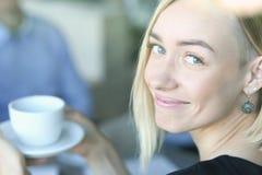 Parler blond de femme aux amis dans un café Photos stock