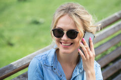 Parler blond mignon à un téléphone portable Photographie stock libre de droits