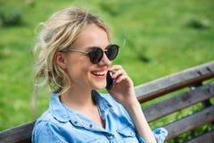 Parler blond mignon à un téléphone portable Photo stock