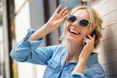 Parler blond mignon à un téléphone portable Photos stock