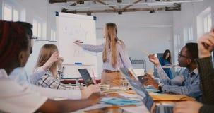 Parler blond sûr heureux de femme d'affaires d'expert du marketing, expliquant le diagramme financier à la formation d'équipe de  clips vidéos