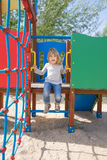 Parler d'enfant monté sur la glissière dans le terrain de jeu Photographie stock libre de droits