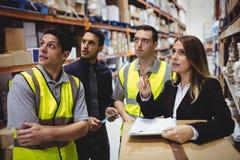 Parler de directeur et de travailleurs d'entrepôt photos stock