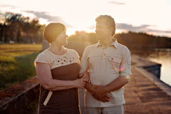Parler de marche de couples pluss âgé riant du coucher du soleil près de la rivière de lac image libre de droits