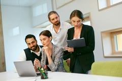 parler de sourire de contact d'ordinateur portatif de bureau de cmputer d'homme d'affaires d'affaires à utiliser la femme Travail Photo libre de droits