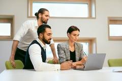 parler de sourire de contact d'ordinateur portatif de bureau de cmputer d'homme d'affaires d'affaires à utiliser la femme Travail Photos libres de droits