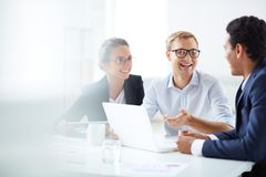 parler de sourire de contact d'ordinateur portatif de bureau de cmputer d'homme d'affaires d'affaires à utiliser la femme Photographie stock