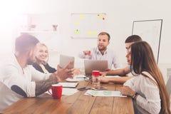 parler de sourire de contact d'ordinateur portatif de bureau de cmputer d'homme d'affaires d'affaires à utiliser la femme Jeunes  Image stock