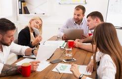 parler de sourire de contact d'ordinateur portatif de bureau de cmputer d'homme d'affaires d'affaires à utiliser la femme Jeunes  Photo libre de droits