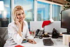 Parler de sourire de femme d'affaires du téléphone fonctionnant dans le jour de Noël de bureau Image libre de droits