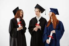 Parler de sourire de trois diplômés heureux tenant des diplômes au-dessus du fond blanc Photo stock