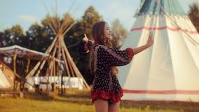 Parler de touristes de jeune femme au téléphone et sourire sur la maison indienne indigène de tipi/tipi de fond Voyageur causant, banque de vidéos