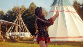 Parler de touristes de jeune femme au téléphone et sourire sur la maison indienne indigène de tipi/tipi de fond Voyageur causant, clips vidéos