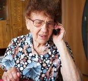 Parler femelle plus âgé pour le téléphone portable Photos libres de droits