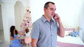 Parler masculin attrayant sur Smartphone dans la chambre à coucher légère sur le fond de son épouse et fille, à qui préparant banque de vidéos