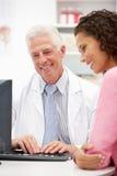 Parler patient femelle avec le docteur aîné Image stock