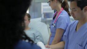Parler patient masculin au personnel médical dans la chambre de secours clips vidéos