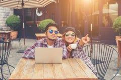Parler potable de jeunes couples de hippie ayant le smilin riant d'amusement Photo stock