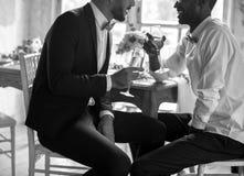 Parler se reposant de couples gais avec des verres de vin ensemble Photographie stock libre de droits