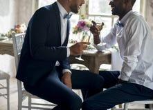 Parler se reposant de couples gais avec des verres de vin ensemble Images stock