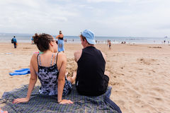 Parler se reposant de plage de garçon de fille Photo libre de droits
