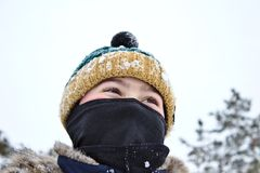 Parler sur le garçon de téléphone dans un chapeau tricoté avec un bubo et un passe-montagne image stock