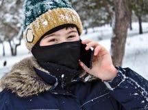 Parler sur le garçon de téléphone dans un chapeau tricoté avec un bubo et un passe-montagne photos libres de droits