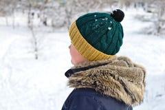 parler sur le garçon de téléphone dans un chapeau tricoté avec un capot de bubo et de fourrure sur une promenade d'hiver image libre de droits
