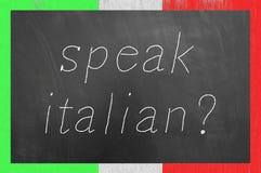 Parlez le texte italien de craie sur le tableau noir de cadre de drapeau photos stock
