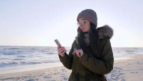 Parli su Internet, femmina si siede nelle reti sociali facendo uso dello smartphone in mare sulla vacanza video d archivio