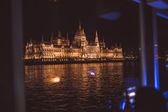 Parliament of Budapest at night illuminated from the Danube river stock photos