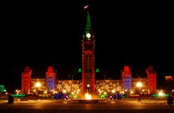Parliament Building and Eternal Flame at Christmas. Canadian parliament building lit up for Christmas with eternal flame in foreground, fully perspective Royalty Free Stock Images