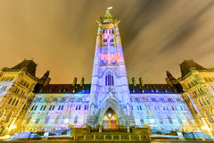 Parliament of Canada. Winter holiday light show projected at night on the Canadian House of Parliament to celebrate the 150th Anniversary of Confederation of Stock Photography