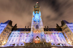 Parliament of Canada. Winter holiday light show projected at night on the Canadian House of Parliament to celebrate the 150th Anniversary of Confederation of Royalty Free Stock Images