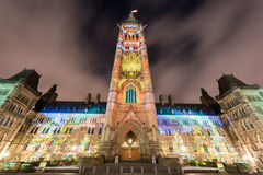 Parliament of Canada. Winter holiday light show projected at night on the Canadian House of Parliament to celebrate the 150th Anniversary of Confederation of Royalty Free Stock Image