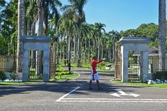 Guard marching in front of the Parliament House in Suva, Fiji with so much green and palm trees decorating the driveway