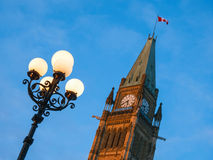 At the Parliament Hill in Ottawa. Lamp post and the clock tower with the Canadian flag Stock Image