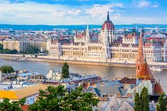 Parliament and riverside in Budapest Hungary during nice sunny summer day against blue sky and clouds. Tourism concept. royalty free stock image