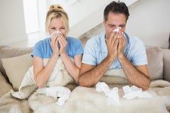 Parlidande från förkylning i säng Arkivfoton