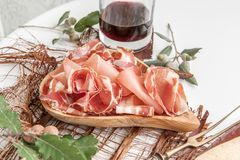 Parma flavored ham in spices, thinly sliced on a white table with red wine bread and antique cutlery.  royalty free stock image