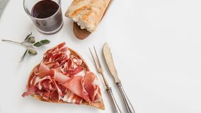 Parma flavored ham in spices, thinly sliced on a white table with red wine bread and antique cutlery. Copy space royalty free stock photo