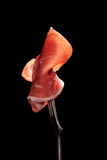 Parma ham on fork isolated. Royalty Free Stock Images