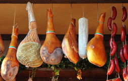 Parma Ham hanging. In a delicatessen shop in Italy stock images