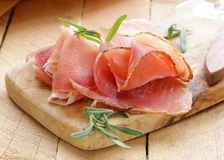 Parma ham (jamon). Sliced ​​on a wooden board royalty free stock photography