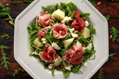 Parma ham and melon salad with mozzarella, rocket and pine nuts.  royalty free stock images