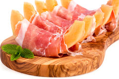 Parma ham and melon. Parma ham and sliced melon starter served on olive wood board over white stock photo