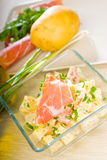 Parma ham and potato salad. Fresh home made parma ham and potato salad,with raw ingredients around with bowls and dishware on a table stock photo